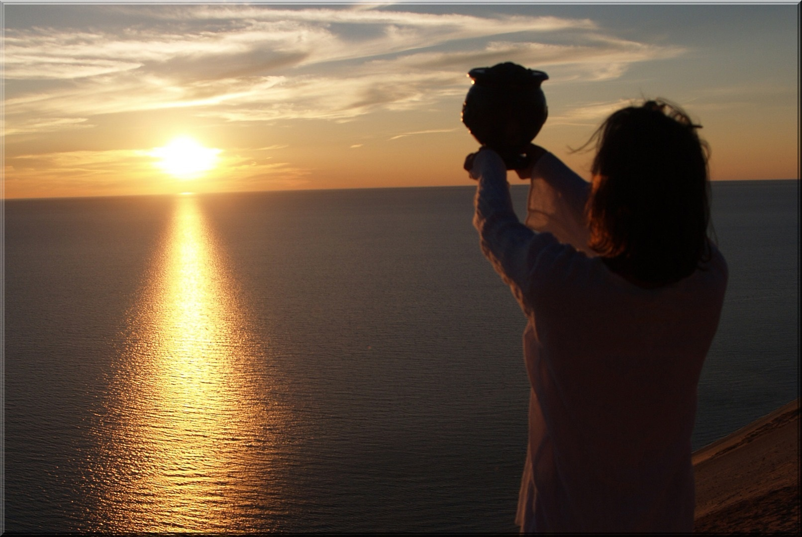 Woman hold final remains of her loved one at sunset