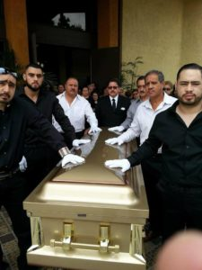 Funeral with friends hands on the casket